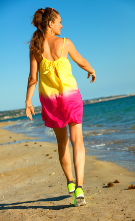 Colorful and wonderfully cheerful mood. Seen from behind healthy woman in colorful dress on the beach in the evening walking