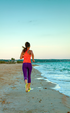 Look Good and feel great. Seen from behind healthy woman jogger in sport style clothes on the seashore in the evening running Archivio Fotografico