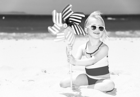 sea, white sand paradise. Portrait of happy modern girl in swimwear on the seacoast with windmill toy
