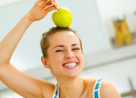 happy young woman holding apple on head Stock Photo