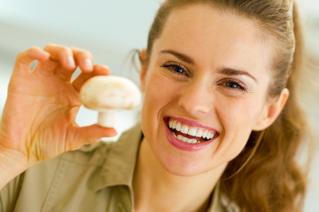 Happy young housewife holding mushroom in kitchen Banco de Imagens