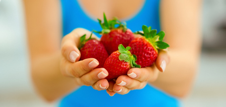 Closeup on young woman showing strawberries Stock Photo