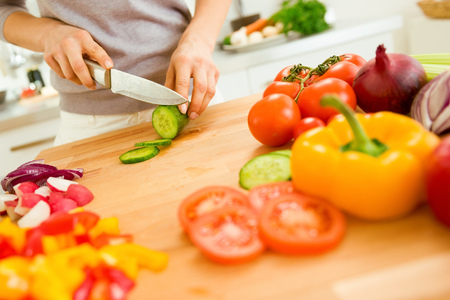 Closeup on young woman slicing vegetables