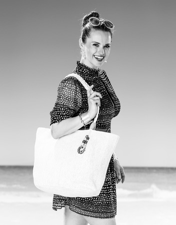 Perfect summer. smiling young woman in summer dress with white beach bag on the seashore Stok Fotoğraf