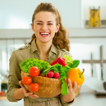 Happy young housewife holding plate full of vegetables in modern kitchen
