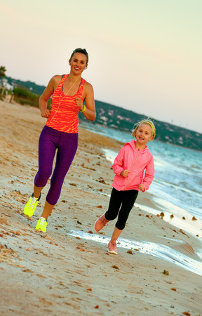 Look Good and feel great. smiling fit mother and child in sport style clothes on the seacoast in the evening running Stockfoto