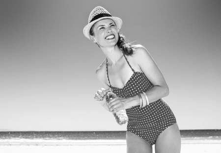 sea, white sand paradise. happy modern woman in swimwear on the beach with water bottle looking into the distance