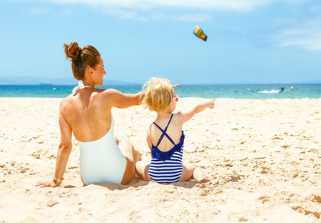 Family fun on white sand. Seen from behind modern mother and child in beachwear on the beach pointing at something
