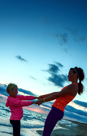 Look Good and feel great. Silhouette. fit mother and child in sport style clothes on the seashore on the sunset having fun time