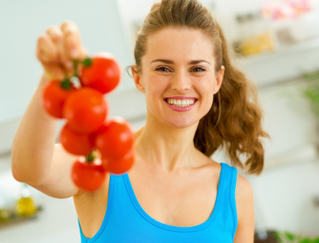 Happy young woman holding bunch of tomato in kitchen Banco de Imagens