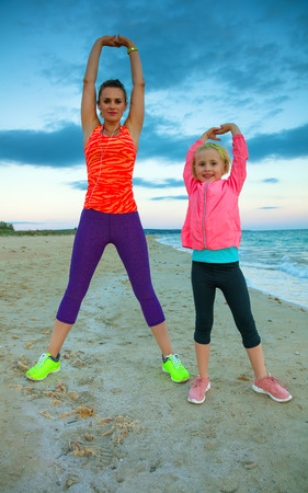 Look Good and feel great. happy healthy mother and daughter in sport style clothes on the seacoast in the evening stretching Banco de Imagens