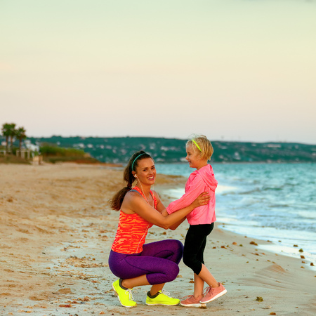 Look Good and feel great. happy young mother and child in sport style clothes on the seashore in the evening having fun time