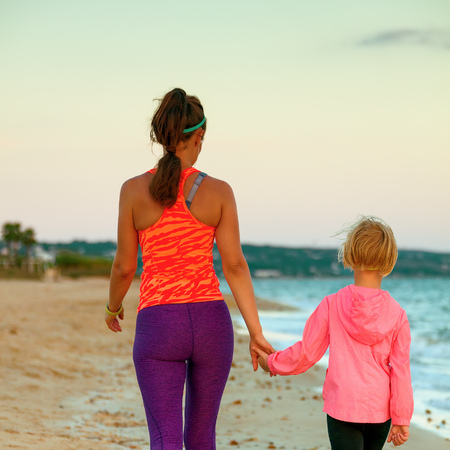 Look Good and feel great. Seen from behind active mother and child in sport style clothes on the seacoast in the evening walking