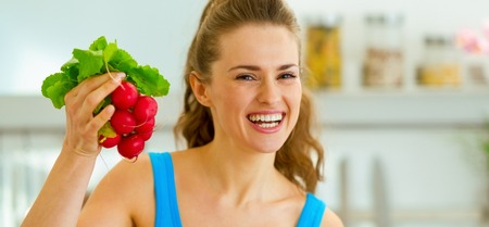 Smiling young woman holding bunch of radishes
