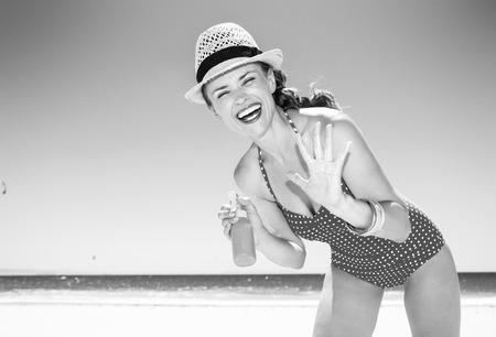 sea, white sand paradise. smiling modern woman in swimwear on the seacoast applying sun cream Foto de archivo - 100136858