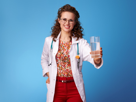 smiling pediatrist woman in white medical robe giving glass of water isolated on blue background