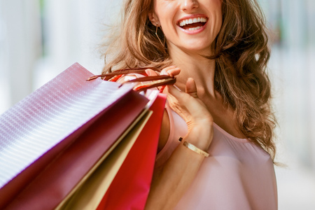 A brown-haired woman holding three shopping bags - brown, gold, and red - over her right shoulder looks back at someone who is making her laugh.