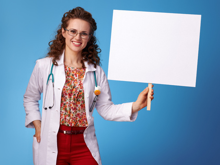 happy paediatrist woman in white medical robe showing placard on blue background