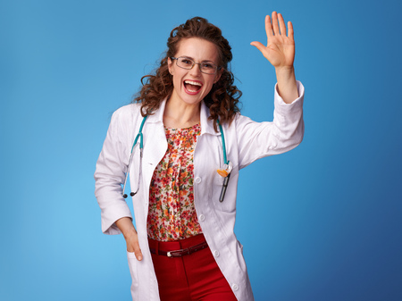 happy pediatrist woman in white medical robe greeting against blue background