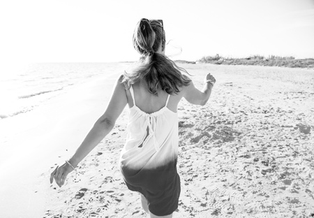 wonderfully cheerful mood. Seen from behind young woman in dress on the beach in the evening walking