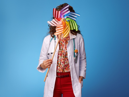 pediatrist woman in white medical robe holding colorful windmill in the front of face against blue background Stock Photo