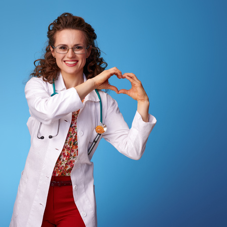 smiling paediatrist doctor in white medical robe showing heart shaped hands against blue background Stock Photo