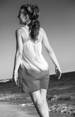 wonderfully cheerful mood. Seen from behind relaxed healthy woman in dress on the seacoast in the evening Stock Photo