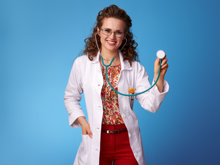 happy paediatrist woman in white medical robe using a stethoscope isolated on blue