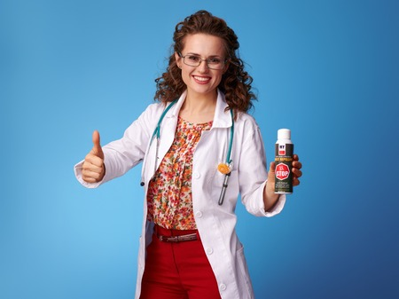 smiling pediatrist woman in white medical robe showing thumbs up and insect repellent on blue background Stock Photo