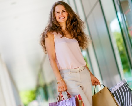 A brown-haired woman wearing muted, gentle shades holds five colourful, patterned shopping bags during a successful shopping spree. Walking outside, she is enjoying the warmth of a summer day. Her smi