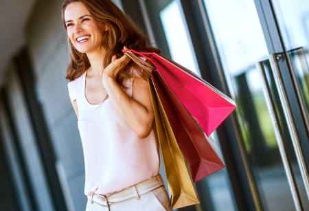 A brown-haired woman holding three shopping bags - gold, brown, and red - over her left shoulder laughs and smiles as she looks out into the distance. 写真素材