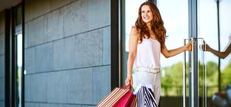Happy young woman with shopping bags entering shop Stock Photo