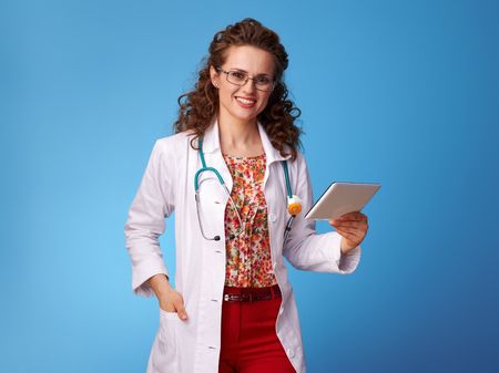 smiling pediatrist woman in white medical robe using tablet PC isolated on blue background