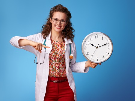 happy paediatrician doctor in white medical robe pointing at clock against blue background Stock Photo