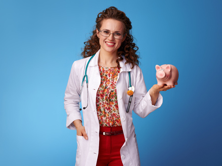 happy pediatrician doctor in white medical robe holding piggy bank on blue background Reklamní fotografie - 100632071