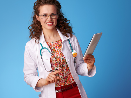 smiling pediatrician woman in white medical robe using tablet PC against blue background
