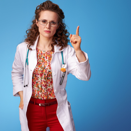 paediatrist doctor in white medical robe with a raised finger on blue background