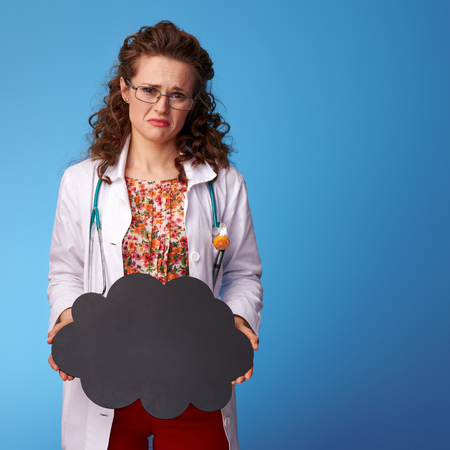 sad paediatrist woman in white medical robe showing black cloud on blue background
