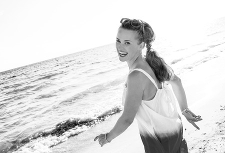 wonderfully cheerful mood. smiling young woman in dress on the beach in the evening walking
