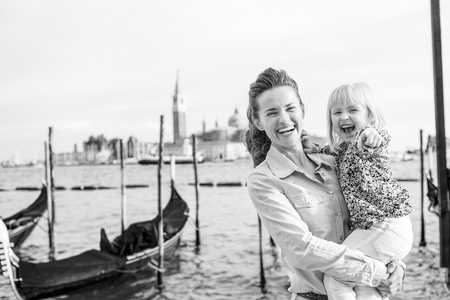 Portrait of happy mother and baby on grand canal embankment in venice, italy Stock Photo