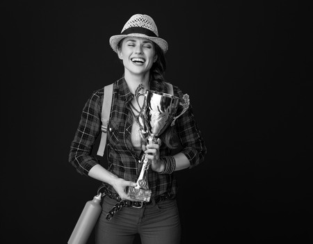 Searching for inspiring places. smiling young woman hiker with backpack hugging goblet against background