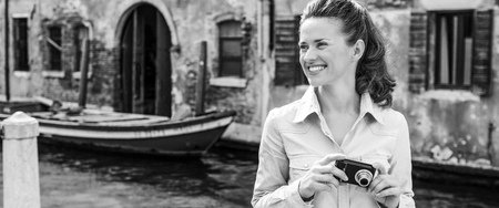 Happy young woman with photo camera looking on copy space while in venice, italy