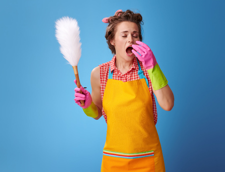 Big cleaning time. modern housewife in a yellow apron with a duster brush sneezing on blue background