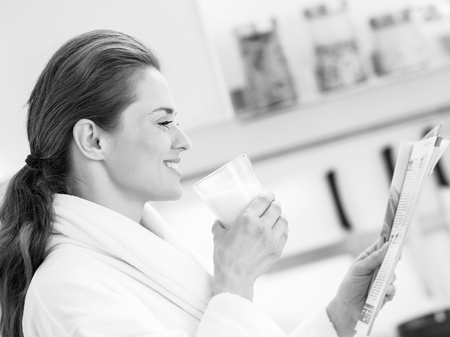 Happy young housewife in bathrobe drinking milk and reading magazine Stock Photo
