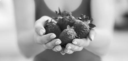 Closeup on young woman showing strawberries Stockfoto