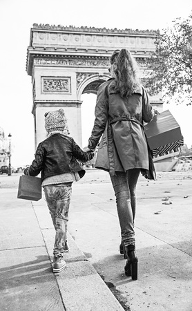 Stylish autumn in Paris. Seen from behind full length portrait of young mother and child with shopping bags in Paris, France walking