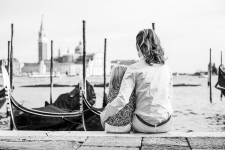Portrait of mother and baby sitting on grand canal embankment in venice, italy. rear view Stock Photo