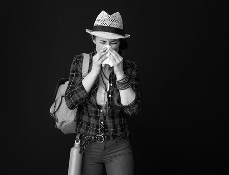Searching for inspiring places. ill traveller woman in a plaid shirt blowing nose against background Stock Photo