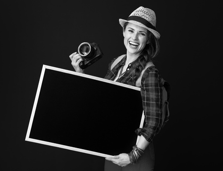 Searching for inspiring places. smiling fit tourist woman in a plaid shirt with DSLR camera showing blank board against background