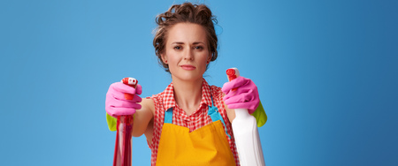 Big cleaning time. cool modern housewife in a yellow apron using bottles of cleaning detergents as guns isolated on blue background Stok Fotoğraf
